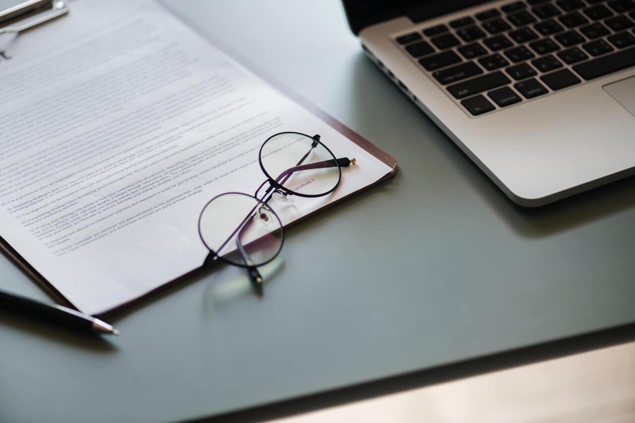 Laptop-dokumenty-i-okulary-na-biurku