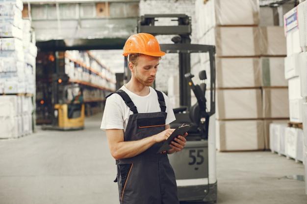 pracujący mężczyzna w pomarańczowym kasku i ubraniu roboczym
